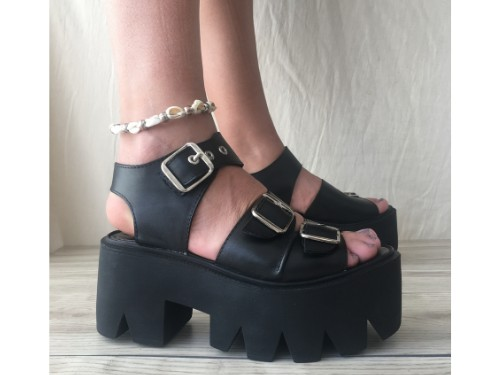 Sandalia de cuero negro con hebillas sobre base de taco y plataforma
